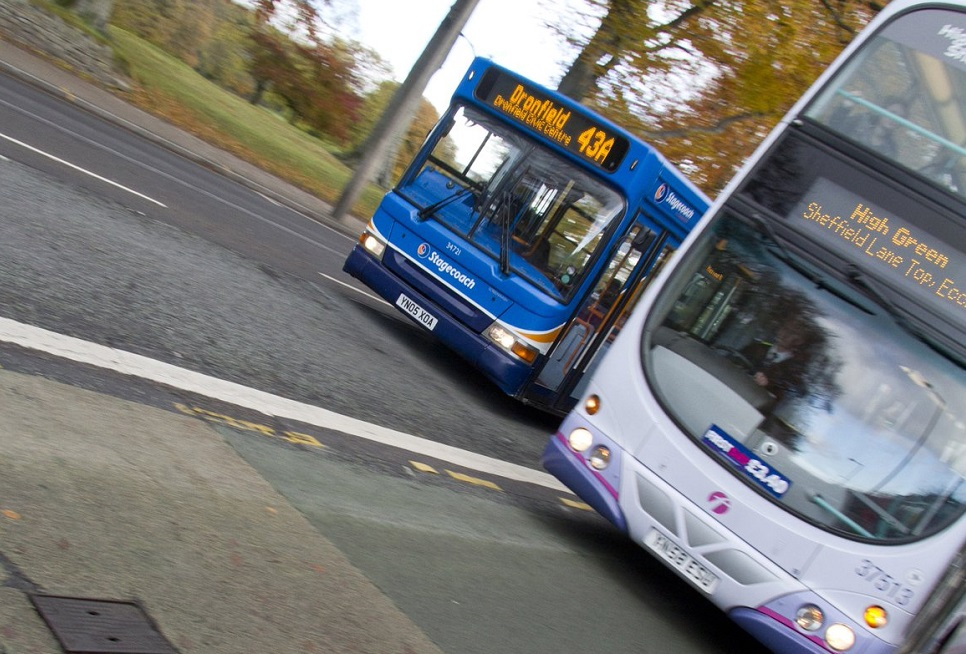 photo of two buses on the road