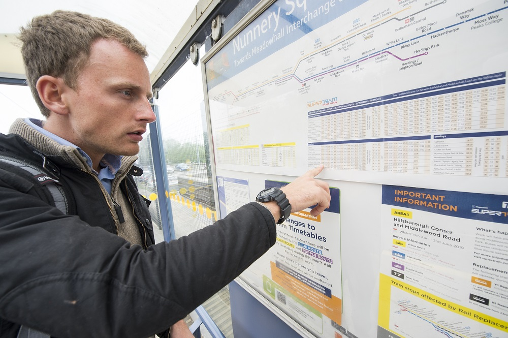 customer looking at timetable at tram stop